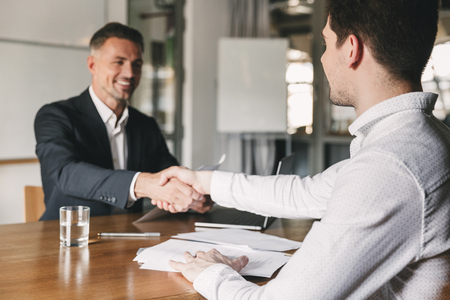 Photo for Business, career and placement concept - successful young man smiling and handshaking with european businessman after successful negotiations or interview in office - Royalty Free Image