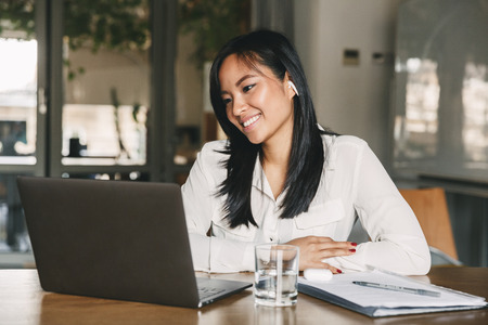 Photo for Photo of adorable asian female worker 20s wearing white shirt and earbud smiling while sitting at table in office and working on laptop - Royalty Free Image