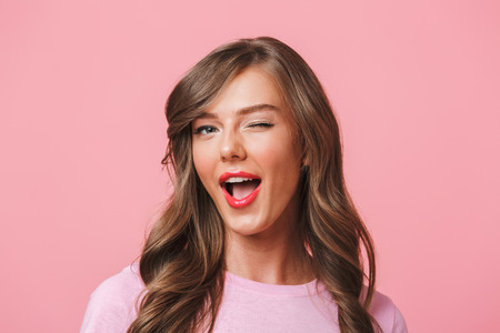 Foto de Image closeup of young attractive woman 20s with long curly hairstyle and seductive look winking at camera with smile isolated over pink background - Imagen libre de derechos
