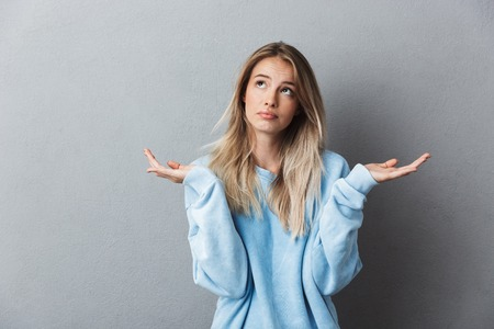 Photo for Portrait of a confused young blonde girl shrugging shoulders isolated over gray background - Royalty Free Image
