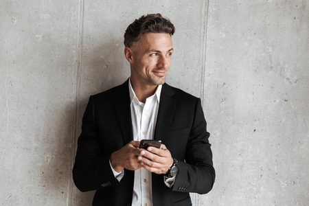 Photo pour Handsome man dressed in suit holding mobile phone and looking away over gray wall background - image libre de droit