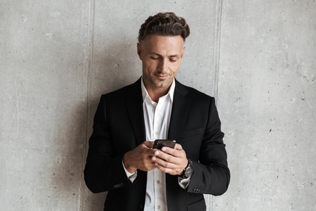 Photo pour Handsome man dressed in suit holding mobile phone over gray wall background - image libre de droit