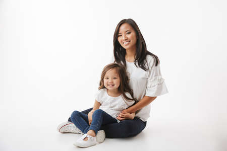 Foto de Image of cute young asian woman mother with her little girl child daughter sitting isolated over white wall background. - Imagen libre de derechos