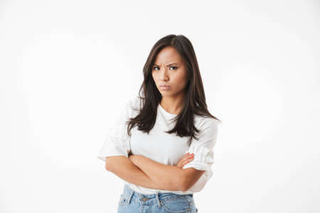 Photo pour Photo of offended or angry asian woman 20s standing with arms crossed and looking at camera with strict gaze isolated over white background closeup - image libre de droit