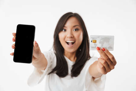 Foto de Blurry photo of happy brunette asian woman wearing casual clothing showing at camera credit card and black smartphone isolated over white background - Imagen libre de derechos