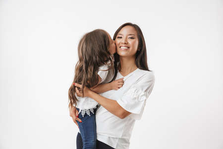 Photo pour Image of happy young asian woman mother with her little girl child daughter isolated over white wall background. - image libre de droit
