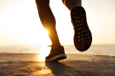 Photo for Back view of male sneakers running at the beach - Royalty Free Image