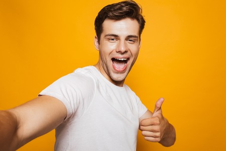 Foto de Portrait of a happy young man taking a selfie with outsretched hand, showing thumbs up gesture isolated over yellow background - Imagen libre de derechos