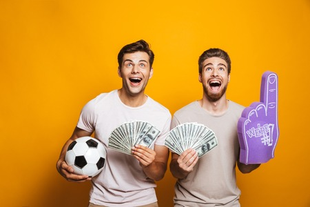 Photo for Portrait of a two cheerful young men best friends with soccer ball showing money banknotes and shouting isolated over yellow background - Royalty Free Image