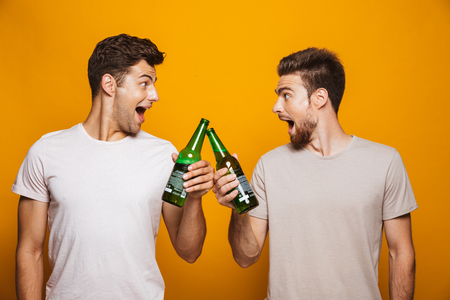 Foto de Portrait of a two cheerful young men best friends toasting with beer bottles isolated over yellow background - Imagen libre de derechos