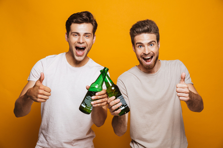 Foto de Portrait of a two happy young men best friends toasting with beer bottles showing thumbs up isolated over yellow background - Imagen libre de derechos