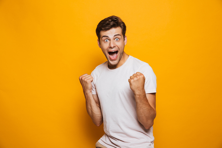 Photo for Portrait of an astonished young man celebrating success isolated over yellow background - Royalty Free Image