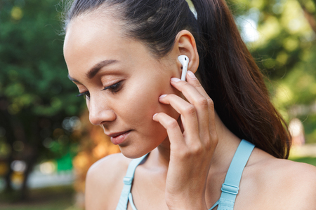 Photo pour Image closeup of beautiful caucasian woman 20s in sportswear using wireless earbud and listening to music during walk in green park - image libre de droit