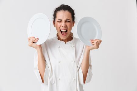 Foto de Portrait of a furious young woman cook dressed in uniform showing two plates isolated over white background - Imagen libre de derechos