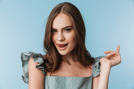 Foto de Picture of pretty young lady showing tongue licking her lips standing isolated over blue background looking camera. - Imagen libre de derechos