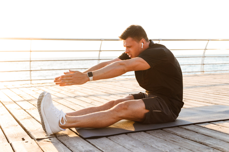 Photo pour Image of handsome young sportsman outdoors on the beach make exercises on sport carpet listening music. - image libre de droit