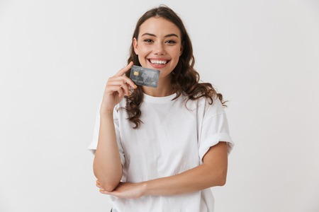 Photo pour Portrait of a smiling young casual brunette woman holding credit card isolated over white background - image libre de droit