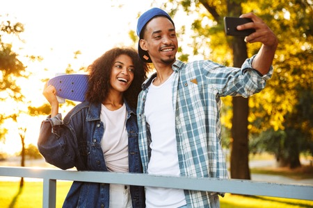 Photo pour Portrait of a happy young african couple with skateboards taking a selfie together at the skate park - image libre de droit