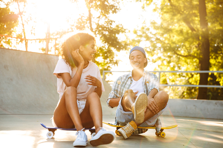 Photo pour Portrait of a laughing young african couple with skateboard sitting together at the skate park - image libre de droit