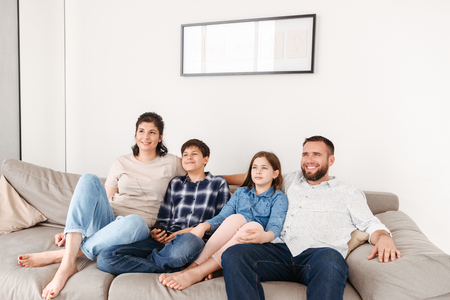 Photo pour Image of caucasian family with two children resting in living room at home and looking at tv together while sitting on sofa - image libre de droit