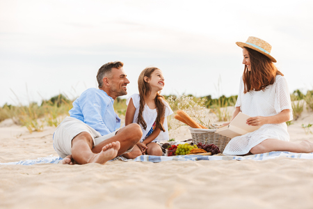Photo for Laughing family with father, mother, daughter having picnic at the beach - Royalty Free Image