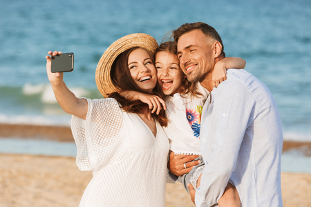 Foto de Happy family spending good time at the beach together, taking selfie - Imagen libre de derechos