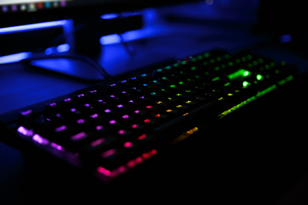 Photo for Close up view of workplace with led rainbow backlight gaming usb keyboard of computer lying on table in dark room - Royalty Free Image
