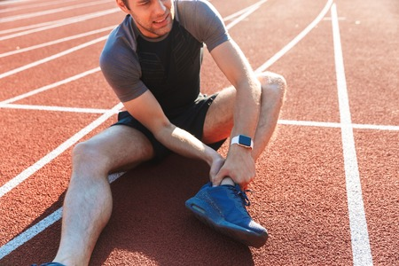 Photo pour Cropped image of a tired sportsman suffering from an ankle pain at the stadium - image libre de droit