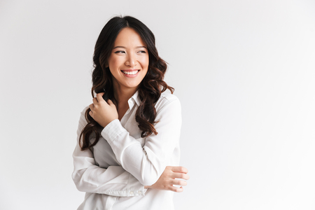 Foto de Photo of optimistic asian woman with long dark hair looking aside at copyspace and laughing isolated over white background in studio - Imagen libre de derechos