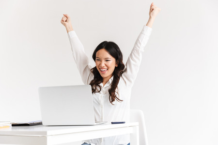 Photo for Photo of excited chinese businesswoman with long dark hair screaming with raised arms and celebrating success while working in office isolated over white background - Royalty Free Image
