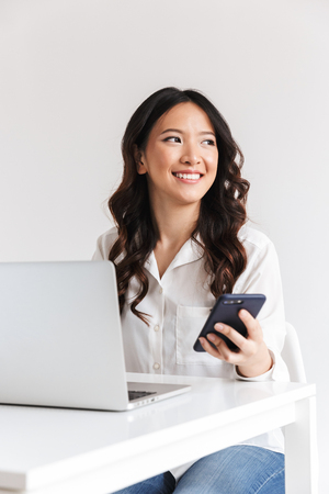 Photo pour Smiling young asian businesswoman holding mobile phone while sitting with laptop computer over white background - image libre de droit