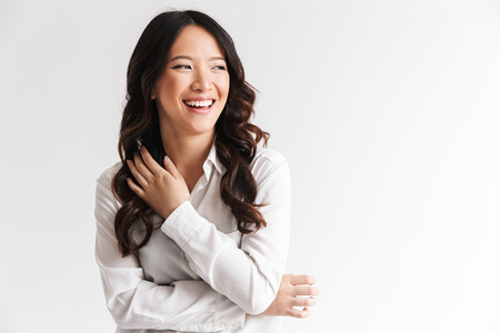 Foto de Image of charming chinese woman with long dark hair looking aside at copyspace and laughing isolated over white background in studio - Imagen libre de derechos
