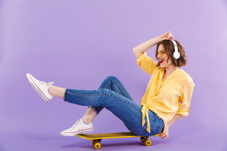 Foto de Portrait of a happy young girl in headphones sitting on skateboard isolated over violet background - Imagen libre de derechos