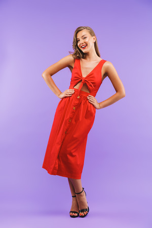 Photo pour Full length portrait of caucasian cute woman 20s wearing red dress smiling at camera standing isolated over violet background - image libre de droit
