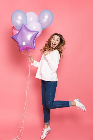 Photo for Full length portrait of a cheerful young woman holding bunch of air balloons while jumping isolated over pink background, pointing away - Royalty Free Image