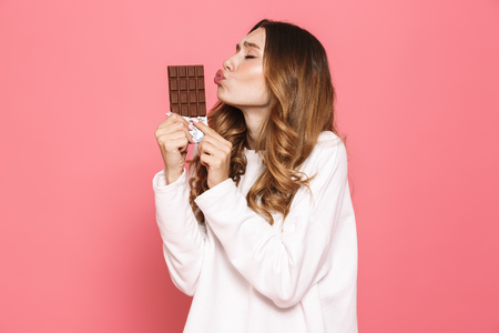 Photo pour Portrait of a happy young woman kissing chocolate bar isolated over pink background - image libre de droit