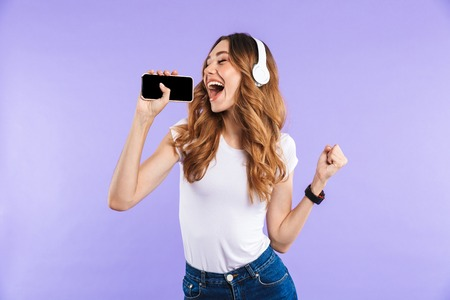 Photo for Portrait of a cheerful young girl holding mobile phone isolated over violet background, listening to music with headphones, singing - Royalty Free Image