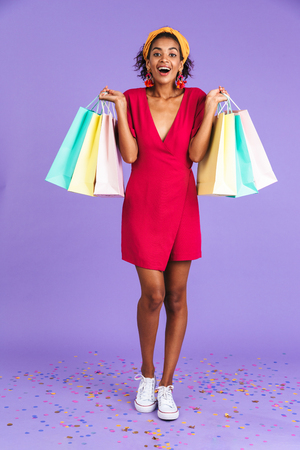 Foto für Full length portrait of a cheerful young african woman in headband standing over violet background, carrying shopping bags - Lizenzfreies Bild