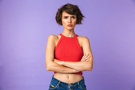 Photo for Image closeup of young displeased woman 20s in casual wear frowning and standing with arms folded isolated over violet background - Royalty Free Image