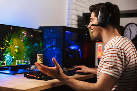 Photo for Image of cheerful gamer man playing video games on computer wearing headphones and using backlit colorful keyboard - Royalty Free Image
