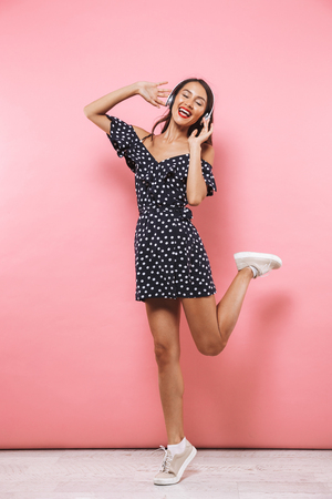 Photo pour Full length image of Happy brunette woman in dress and headphones listening music while jumping and enjoys with closed eyes over pink background - image libre de droit