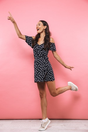 Photo for Full length image of Pleased brunette woman in dress jumping while pointing and looking away over pink background - Royalty Free Image
