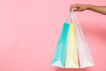 Foto für Cropped image of woman holding packages with purchases over pink background - Lizenzfreies Bild