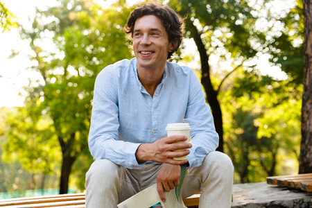 Photo for Smiling young casual man holding newspaper while sitting at the city park, drinking coffee - Royalty Free Image