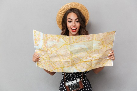 Foto de Image of excited young cute woman wearing hat holding map over grey wall. - Imagen libre de derechos