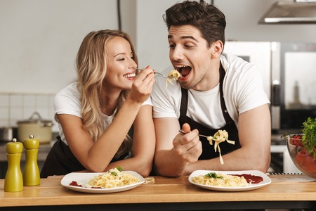 Foto de Image of happy excited young friends loving couple chefs on the kitchen eat tasty pasta. - Imagen libre de derechos