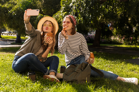 Photo pour Two happy young girls friends having fun at the park, taking a selfie, having a picnic - image libre de droit
