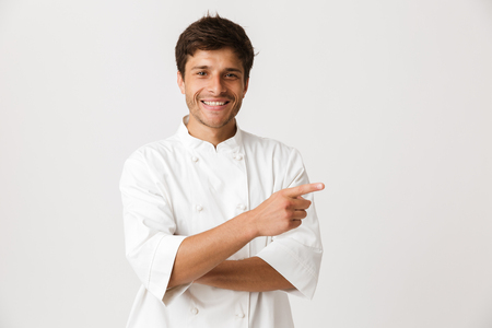 Foto de Image of handsome young chef man standing isolated over white wall background pointing to copyspace. - Imagen libre de derechos