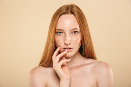 Foto per Beauty portrait of a sensual young topless redhead girl with freckles isolated over beige background - Immagine Royalty Free