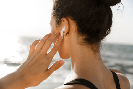Photo pour Close up back view of of young sportswoman at the seaside, listening to music with earphones - image libre de droit